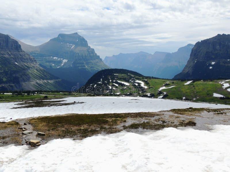 Yendo al camino de Sun, vista del paisaje, campos de nieve en Parque Nacional Glacier alrededor de Logan Pass, lago ocultado, ras foto de archivo