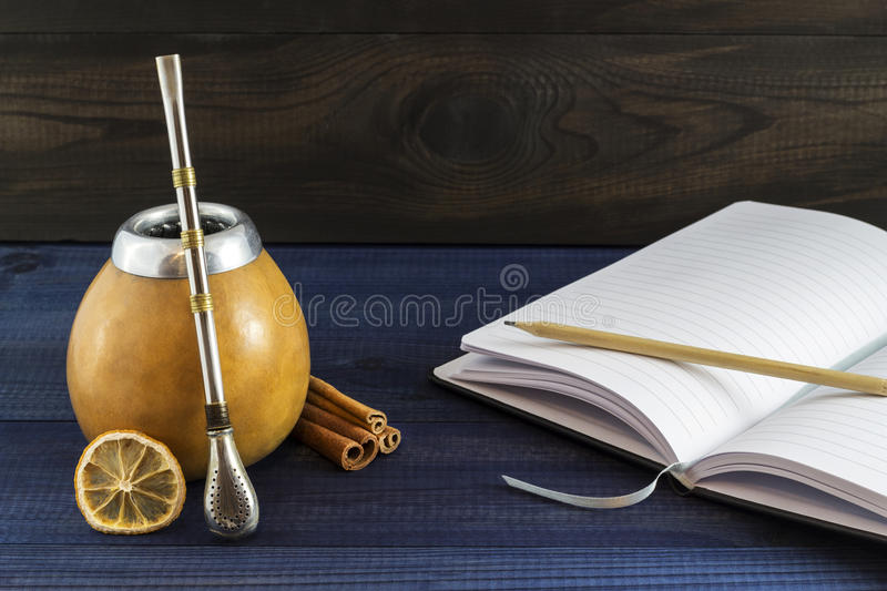 Yerba mate in gourd matero with spices and open notepad. Image with copy space stock photo
