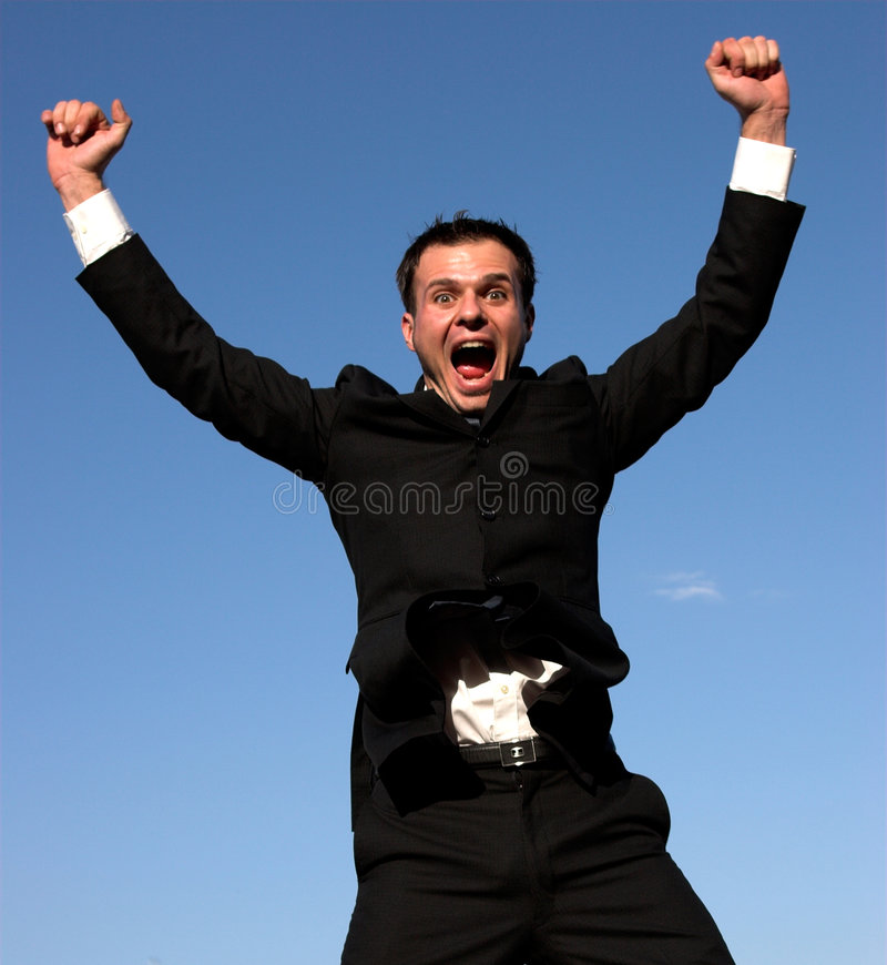 YES!!. Young businessman with a blue sky behind him, jumping stock photo