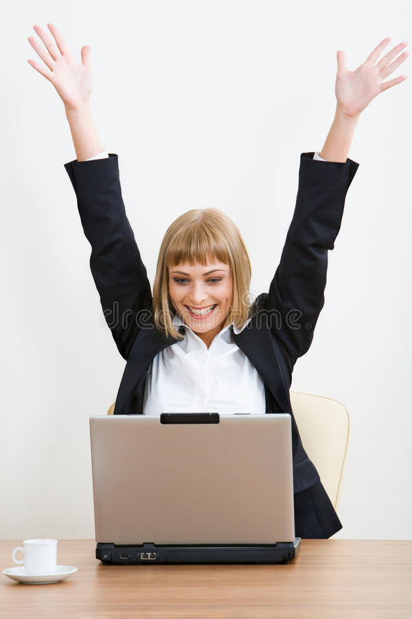 Yes!!!. Portrait of smiling businesswoman with raised hands sitting at the table with the opened laptop and a cup on it
