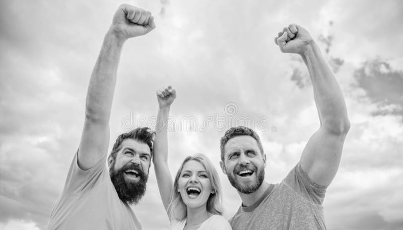 Yes we can. Woman and men look confident successful sky background. Threesome stand happy confidently with raised fists. Behaviors of cohesive team. Celebrate royalty free stock photo