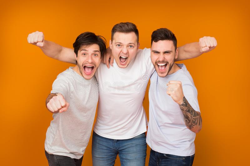Yes. Cheerful men shouting and celebrating victory royalty free stock photo