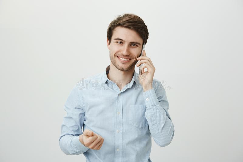Yes, deal almost in our hands. Portrait of successful handsome businessman in casual blue shirt, talking on smartphone. And clenching fist, smiling broadly at stock photos