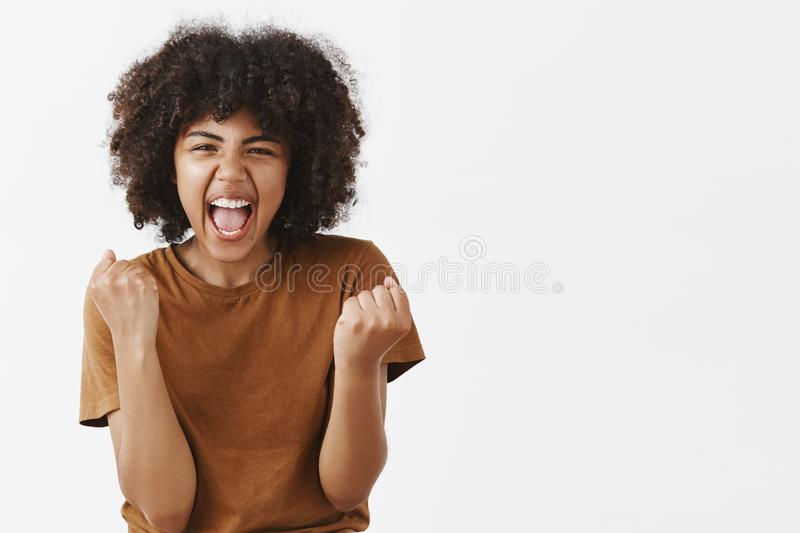 Yes we did it team. Portrait of joyful excited and emotive happy dark-skinned female student cheering for favorite team stock photography