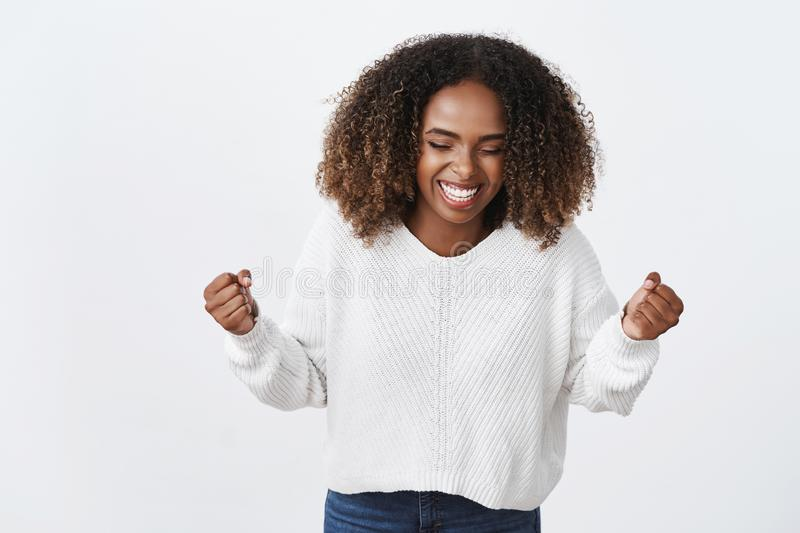 Yes finally ahievement. Portrait charming african-american smiling happy woman clench fists victory gesture triumphing. Perform success dance movement celebrate royalty free stock photography
