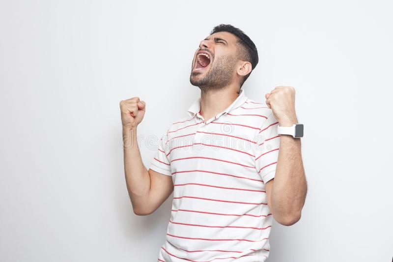 Yes I win. Portrait of happy screaming handsome bearded young man in striped t-shirt standing with fists and rejoicing or. Celebrating his victory. indoor royalty free stock photo