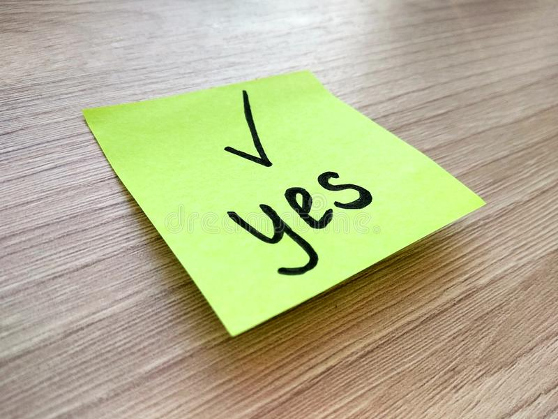 Yes message on sticky note on wooden background. Agreement and compliance concept. Yes message on sticky note on wooden table background. Agreement and stock image
