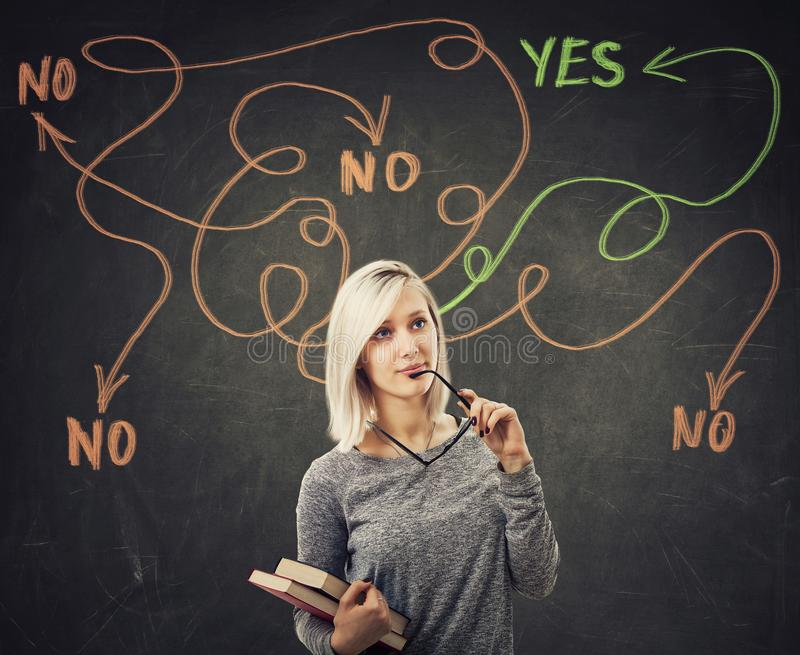 Yes or no arrow. Hard thinking serious smart woman holding books over blackboard background finding the answer to her questions as curves arrows from head royalty free stock image