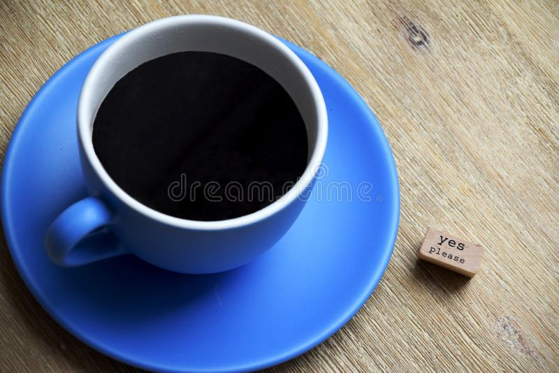 Yes please to coffee. Black coffee in a blue cup on a blue plate on a wooden table. Next to the cup is a sign saying yes please. Close up photo stock image