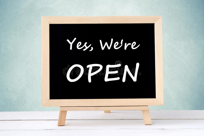 Yes, we& x27; re open on blackboard over green wall background royalty free stock image