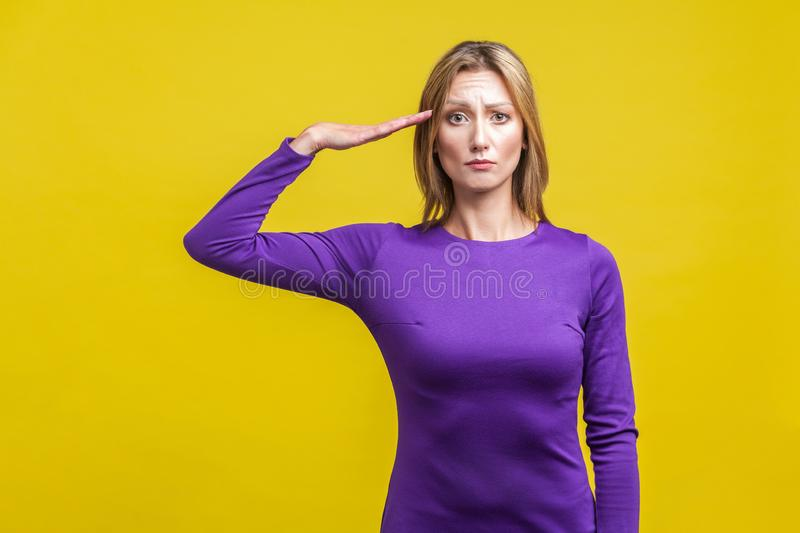 Yes sir! Portrait of serious woman saluting with hand near head. indoor studio shot isolated on yellow background royalty free stock photos