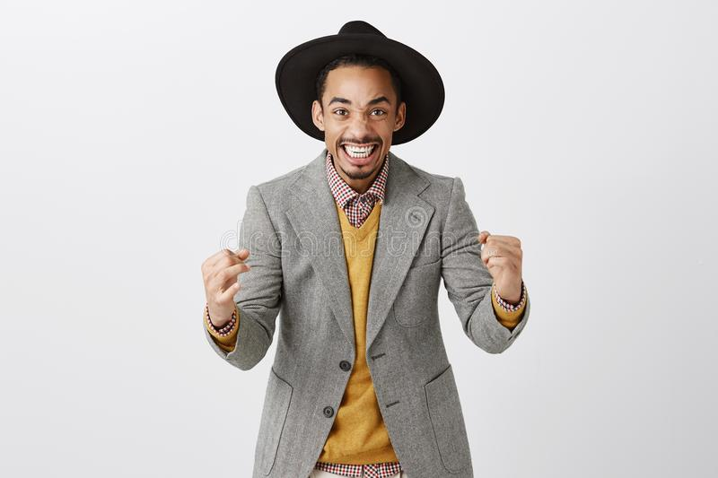 Yes, it is success. Portrait of cheerful good-looking african male in black hat and gray jacket, clenching fists and royalty free stock photos