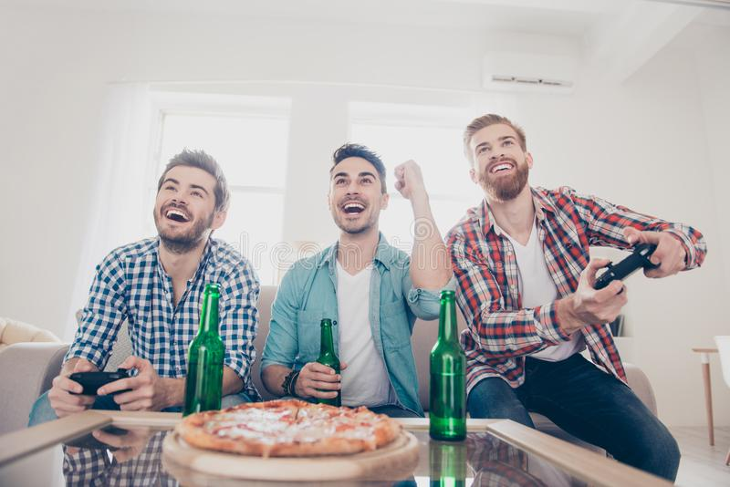 Yes! Team of winners! Bachelor men`s life. Low angle of three happy joyful men, sitting on sofa and playing video games with beer. And pizza, smiling, gesturing stock image