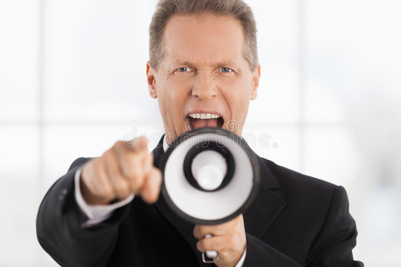Yes, You!. Portrait of confident mature man in formalwear shouting at megaphone and pointing camera royalty free stock images