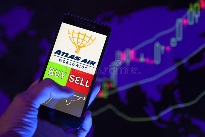 YESSENTUKI, RUSSIA - July 27, 2019: Company logo Atlas Air Worldwide Holdings Inc aaww on smartphone screen, hand of trader hold royalty free stock photography