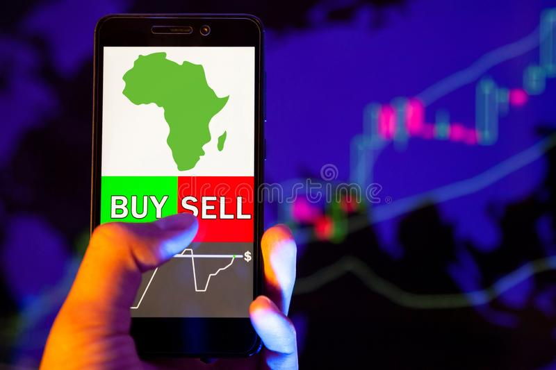 Company logo VanEck Vectors Africa Index ET on smartphone screen, hand of trader holding mobile phone showing BUY or SELL on backg. YESSENTUKI, RUSSIA - July 25 royalty free stock photos