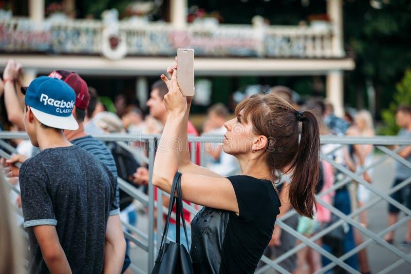 Yessentuki Stavropol terytorium, Rosja, Sierpień,/- 12, 2017: kobieta przy koncertów krótkopędami na telefonie outdoors fotografia stock