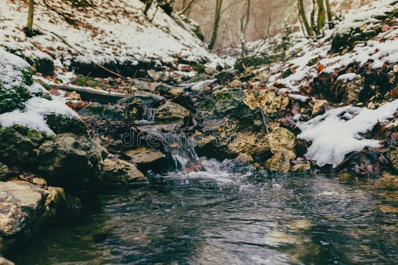 A tiny water stream during the winter stock photo