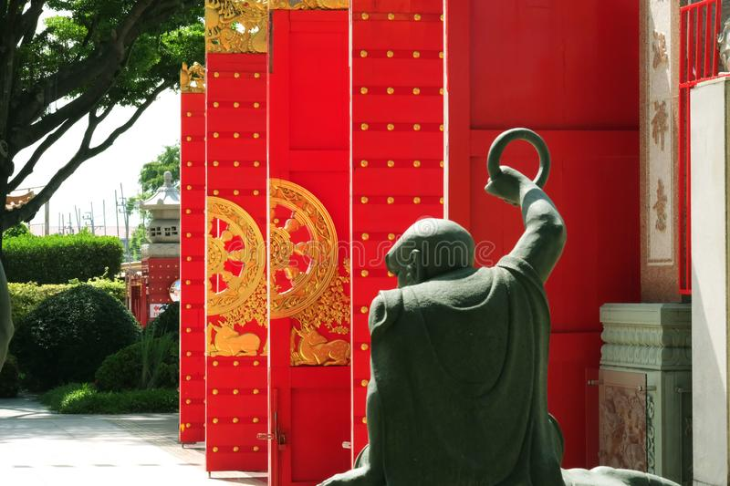 Red doors behind a Chinese angel statue. Yesterday I went to a beautiful Chinese temple far away from home and take pictures stock photography