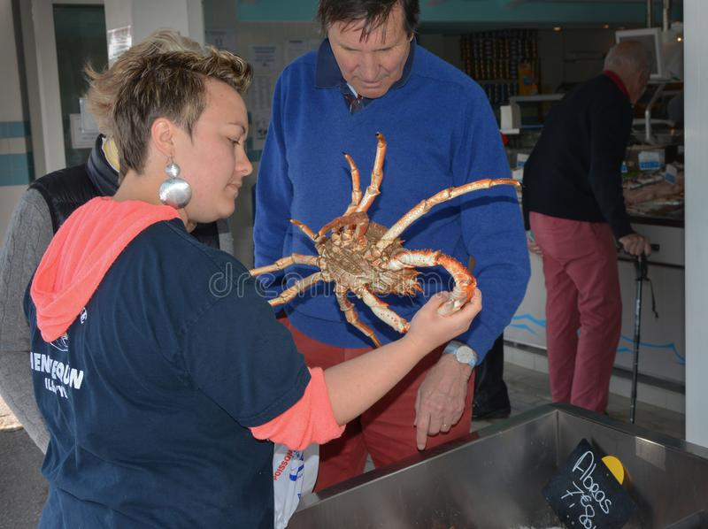 ` YEU, FRANKREICH ILE D - 23. MAI 2016: Der Verkäufer bietet die Krabbe dem Käufer in der Fischabteilung des Speichers an stockfoto
