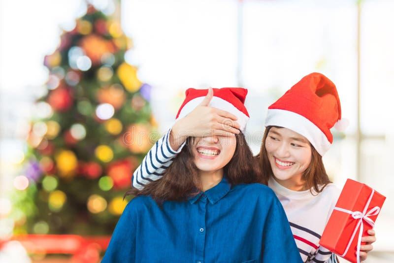 Yeux étroits d'amie à la main pour étonner l'ami en donnant le cadeau de Noël en partie photo stock