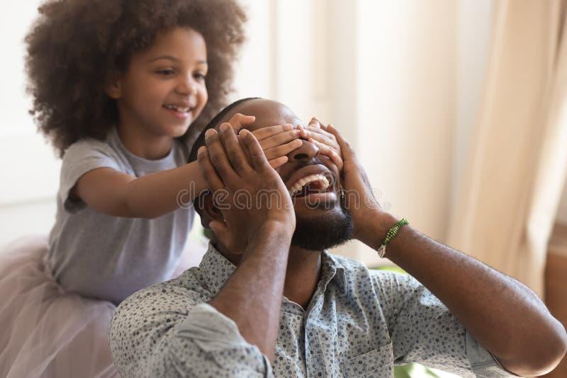 Yeux étroits de fille africaine mignonne d'enfant faisant la surprise pour le papa photos stock