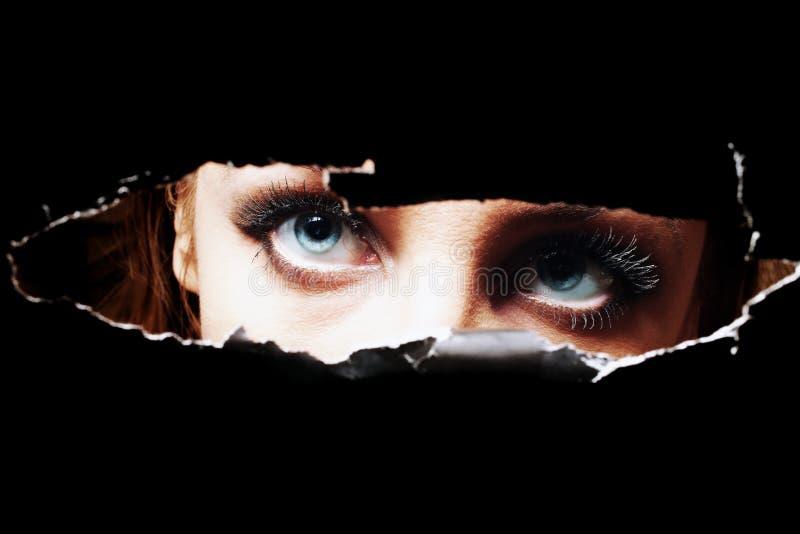 Yeux bleus de jeune femme piaulant par un trou photos libres de droits