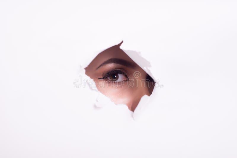 Yeux d'une jeune femme curieuse jetant un coup d'oeil par un trou d?chir? en affiche de livre blanc avec le beau maquillage images libres de droits
