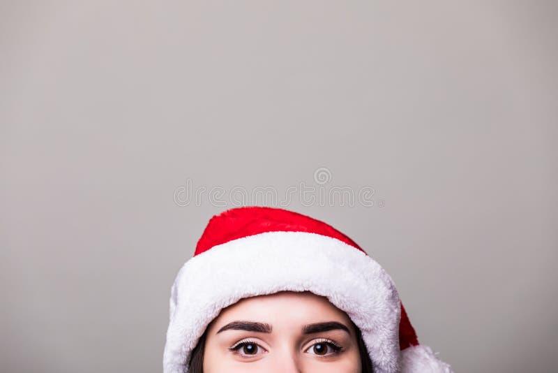 Yeux de fille dans le chapeau de Santa sur le fond gris photographie stock