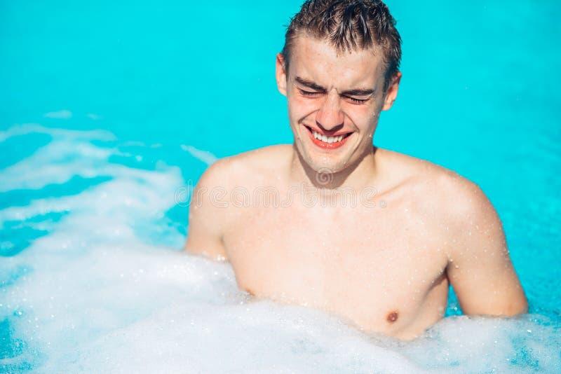 Yeux de frottage de jeune homme dans la piscine Activité d'été La pollution de verre de contact, nageant en chlore a souillé la p photographie stock