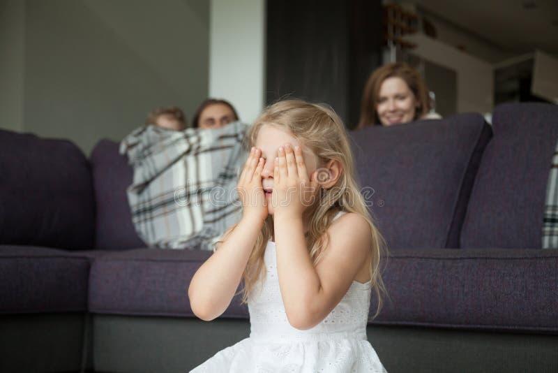 Yeux fermants de petite fille jouant le cache-cache avec la famille images stock