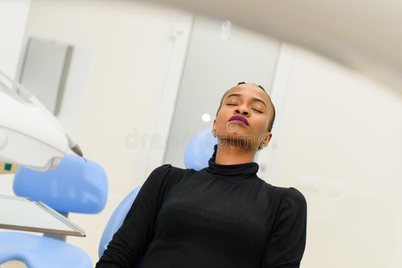 Yeux fermants se reposants de patient noir ethnique afro-américain sur la chaise dentaire attendant son dentiste photo libre de droits