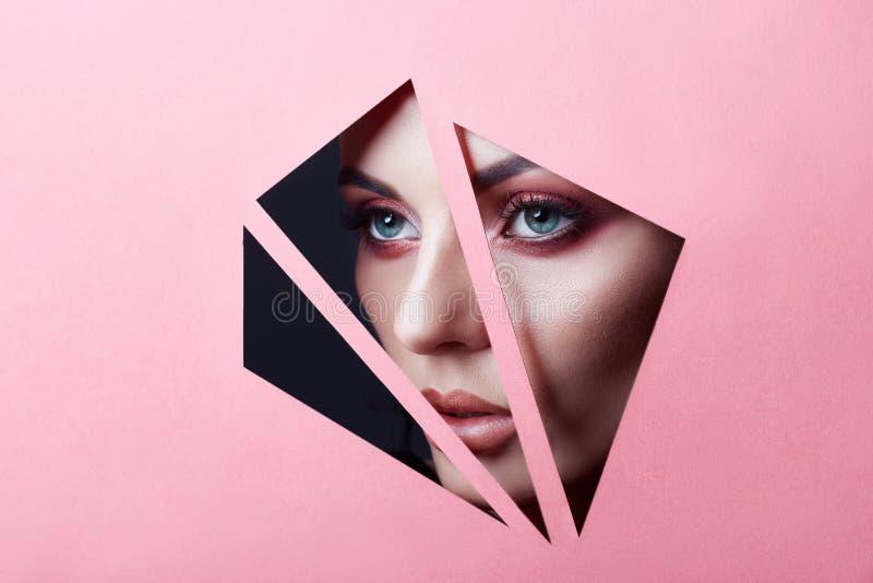 Yeux rouges de maquillage de visage de beauté d'une jeune fille dans un trou fendu de papier rose Femme avec l'ombre rougeoyante  photos stock