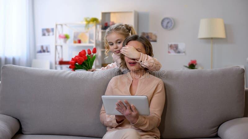 Yeux se fermants de mères de fille, préparant pour présenter des tulipes, surprise de vacances images stock