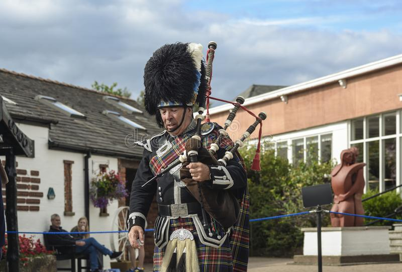 YGRETNA GREEN, SCOTLAND / UNITED KINDOM - AUGUST 13, 2016: Piper in traditional scottish kilt. Male piper in traditional scottish kilt in front of buildings in royalty free stock photos