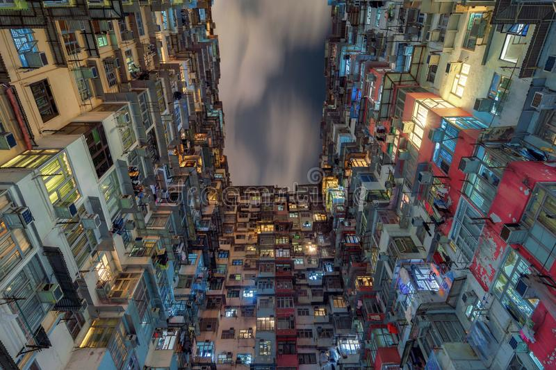 Yick Fat Building, Quarry Bay, Hong Kong. Residential area in old apartment. High-rise building, skyscraper with windows of. Architecture in urban city at night royalty free stock images