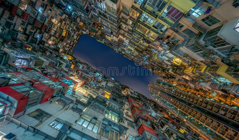 Yick Fat Building, Quarry Bay, Hong Kong. Residential area in old apartment. High-rise building, skyscraper with windows of. Architecture in urban city at night stock image