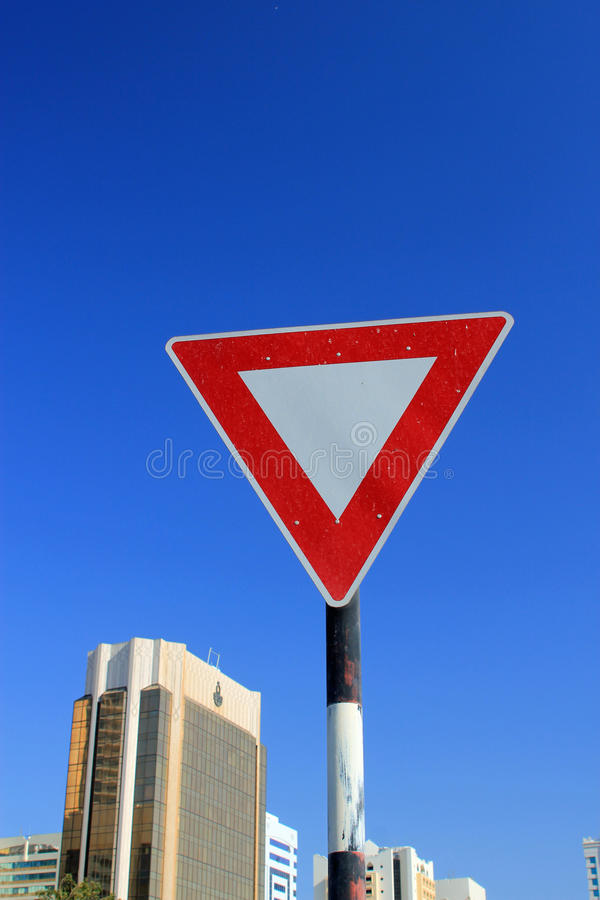 Yield triangle traffic sign. Against a blue sky with modern buildings in the background symbolizing the need to give way stock photos