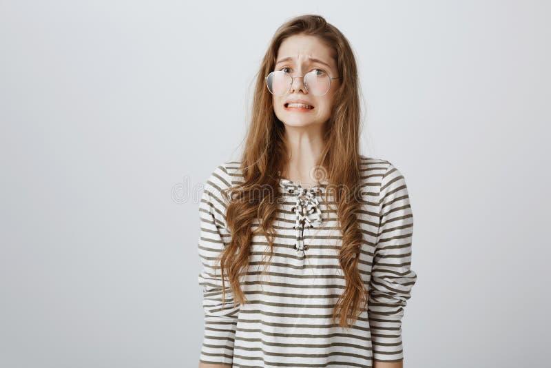 Yikes, coisa má aconteceu Retrato de adolescente caucasiano nervoso confuso nos vidros, olhando de sobrancelhas franzidas, aperta fotografia de stock royalty free