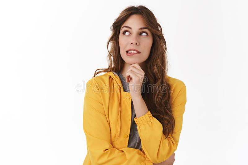 Yikes shall I. Doubtful pretty caucasian curly-haired young woman yellow jacket smirking look away hesitant pondering stock photo
