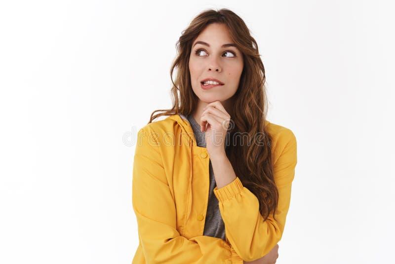 Yikes soll ich Schauen die gelockte gelbe smirking Jacke der jungen Frau des zweifelhaften hübschen Kaukasiers weg das zögernde E stockfoto