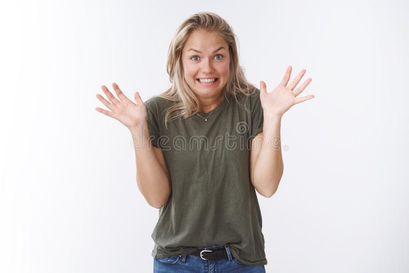 Yikes sorry. Studio shot of awkward cute blond woman raising palms in apology gesture smiling excusing for not making. Mistake on purpose posing guilty against stock photos