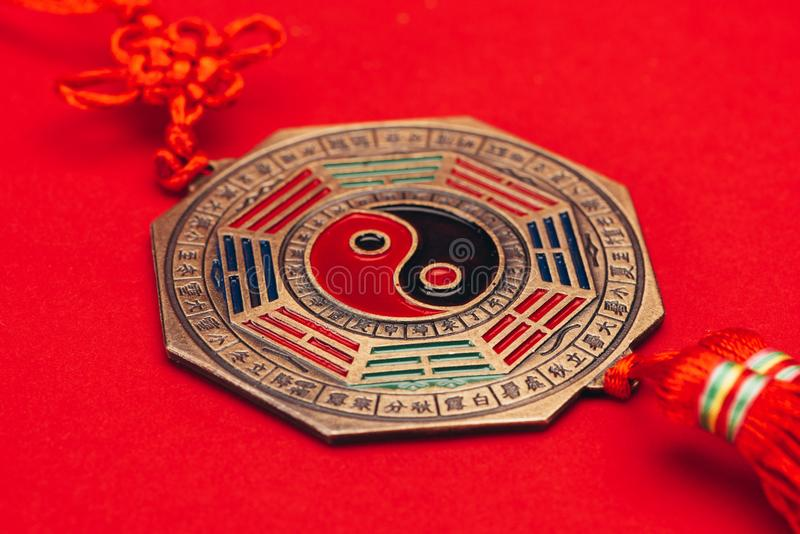 Yin för traditionell kines och yang amulett på röd yttersida arkivbilder