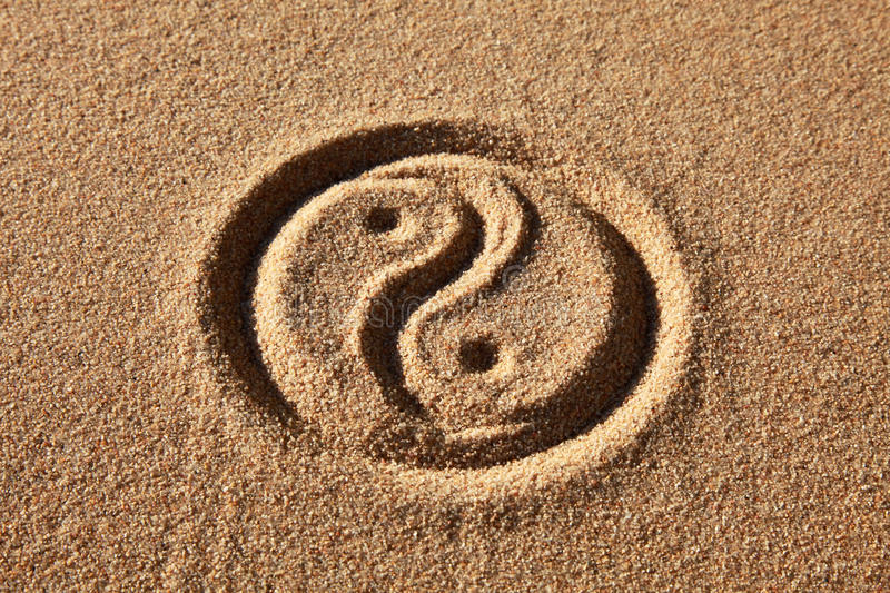 Yin and Yang. The Yin and Yang symbol is written in sandy ground
