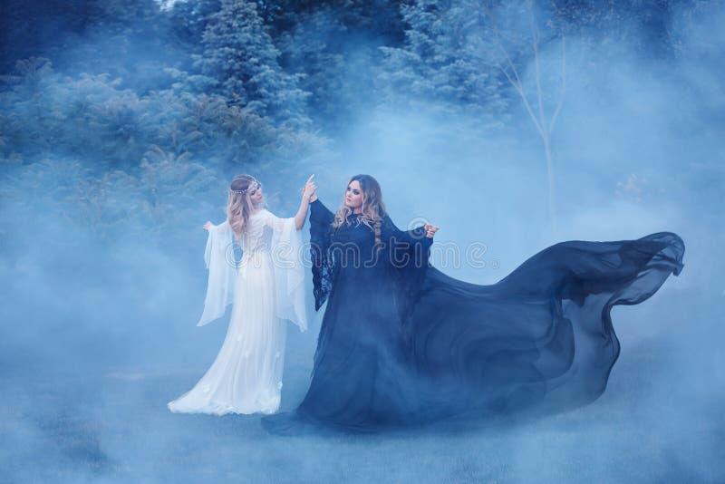 Yin yang de dos mujeres en la niebla El mago oscuro resuelve el duende ligero una bruja Las brujas poderosas están bailando en fotos de archivo