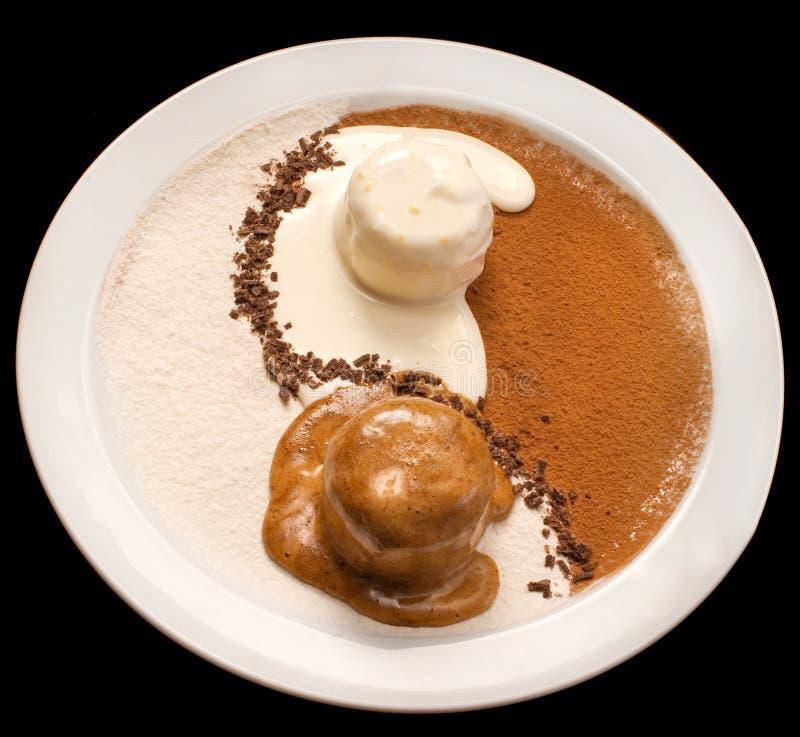 Yin Yang decoration of chocolate and vanilla ice cream. On a white plate, scoop, gelato, dairy, dessert, food, frozen, brown, closeup, sweet, icecream, dark royalty free stock photography