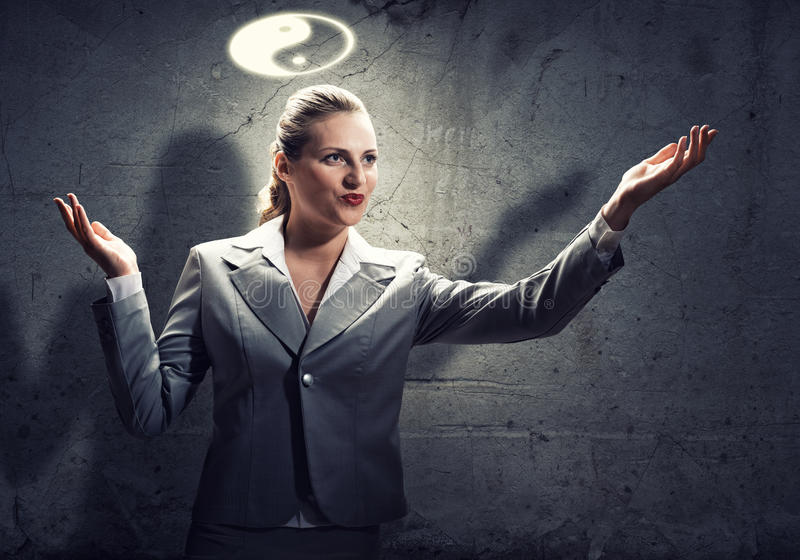 Yin yang philosophy. Young gesturing businesswoman with yin yang sign above head stock photography