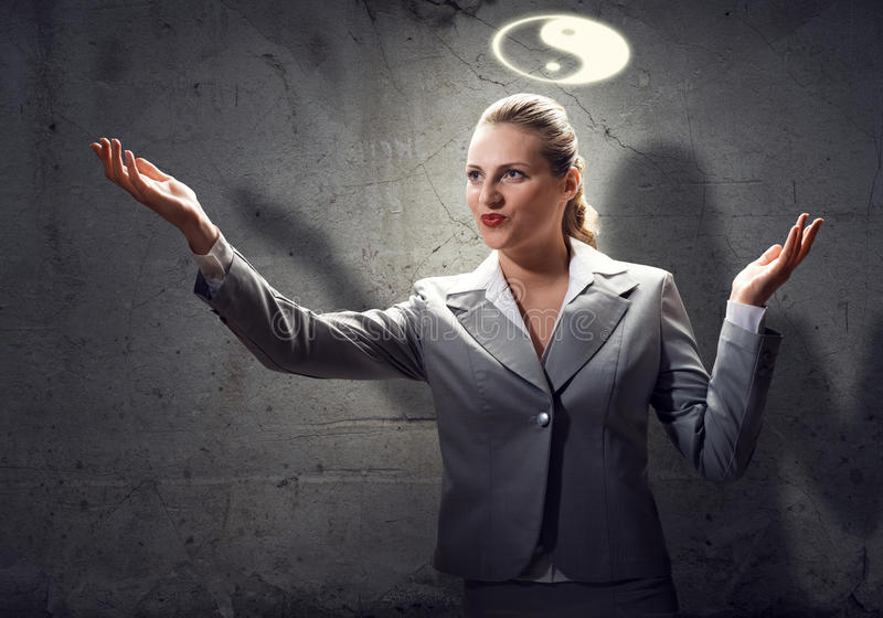 Yin yang philosophy. Young gesturing businesswoman with yin yang sign above head stock image
