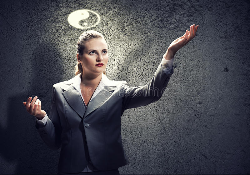 Yin yang philosophy. Young gesturing businesswoman with yin yang sign above head stock photos