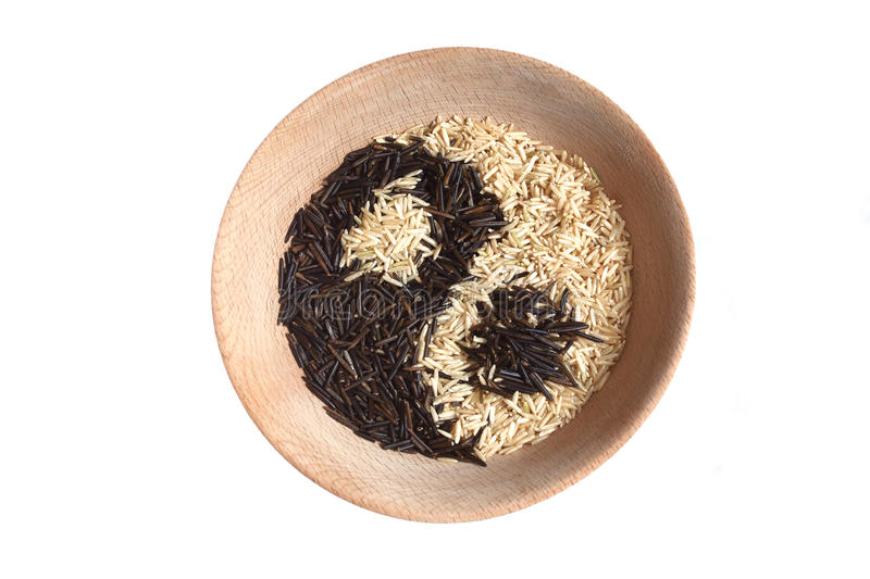 Yin and yang sign made of rice in wooden bowl. Light brown wooden bowl filled with white and brown rice. Yin and Yang symbol. White background stock photos